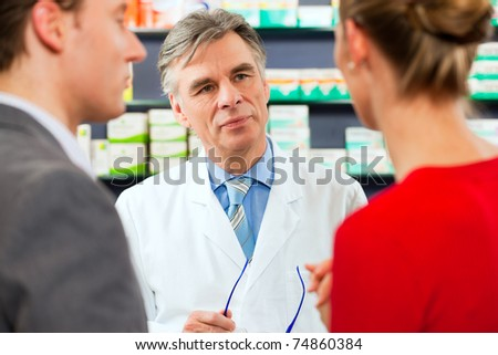 Pharmacist is consulting customers in his pharmacy - a man and a woman - stock photo