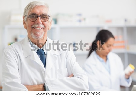 Pharmacist looking at camera with arms crossed in hospital - stock photo