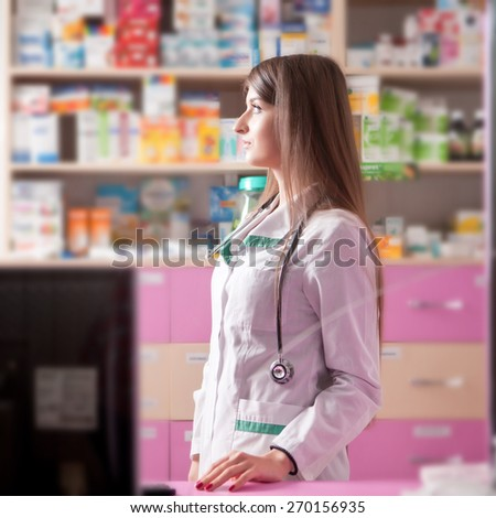Pharmacist looking away at her working desk. Blurred drugs on background. Young and successful pharmacist - stock photo