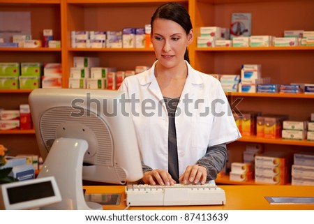 Pharmacist making an online order in a pharmacy - stock photo