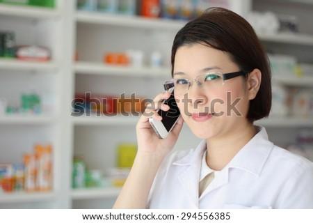 pharmacist on the phone at pharmacy drugstore - stock photo