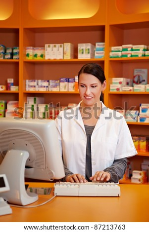Pharmacist ordering medicine with computer in a drugstore - stock photo