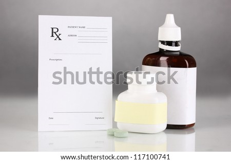 Pharmacist prescription with drops and pills isolated on gray - stock photo