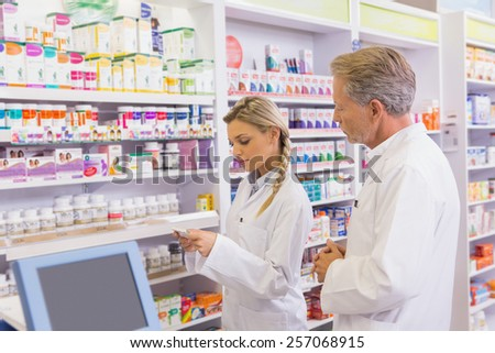 Pharmacist showing medication to his trainee in the pharmacy - stock photo