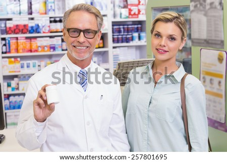 Pharmacist showing medicine jar at the hospital pharmacy