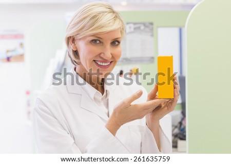 Pharmacist showing medicine jar at the hospital pharmacy - stock photo