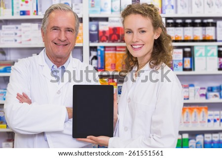 Pharmacist showing tablet pc at hospital pharmacy - stock photo