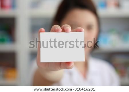 pharmacist showing white blank medicine box with pharmacy store shelves background - stock photo