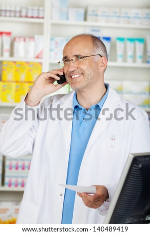 pharmacist standing in pharmacy and calling on the phone - stock photo