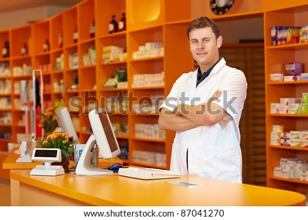 Pharmacist standing with arms crossed in a pharmacy - stock photo