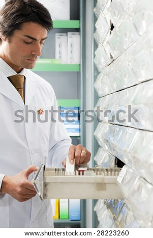 pharmacist taking medicine from drawer. Copy space - stock photo
