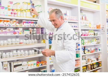 Pharmacist taking medicine from shelf in the pharmacy - stock photo