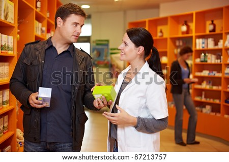 Pharmacist talking to a man in a pharmacy - stock photo