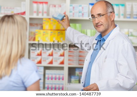 pharmacist talking to female client while taking medicine of the shelf - stock photo