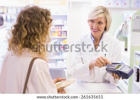 Pharmacist using card machine at pharmacy - stock photo