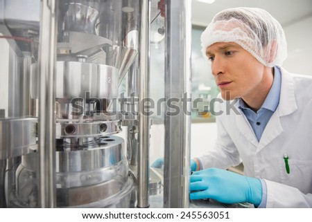 Pharmacist using machinery to make medicine at the hospital pharmacy - stock photo