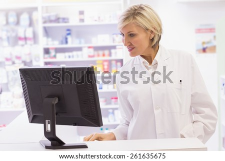 Pharmacist using the computer at pharmacy - stock photo