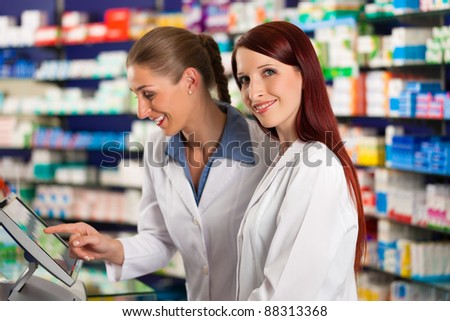 Pharmacist with female assistant in pharmacy standing in front of shelf with drugs - stock photo