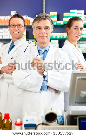 Pharmacist with his team standing in pharmacy or drugstore in front of shelves with pharmaceuticals - stock photo