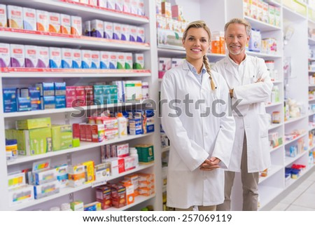 pharmacist with his trainee standing and smiling at camera in the pharmacy - Pharmacist Trainee