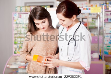 Pharmacist woman showing product to custumer interior of real pharmacy. Customer care. Healthcare business - stock photo