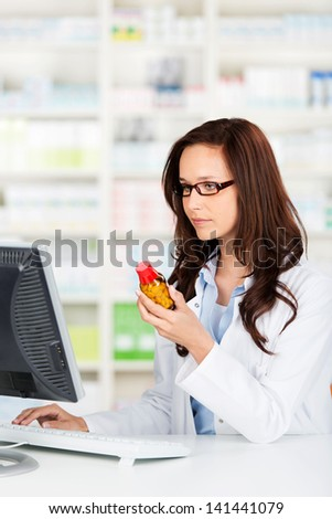 Pharmacist working on her computer checking a bottle of pills before dispensing them to a patient - stock photo