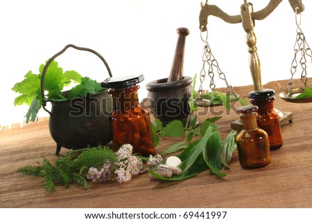 Pharmacists scale with mortar, old pot, apothecary jar and fresh herbs - stock photo