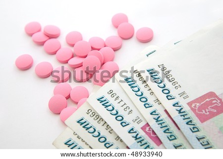 Pharmacological pills and money a white background - stock photo