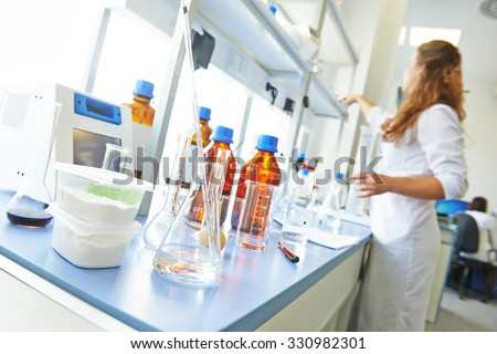 Pharmacy and chemistry theme. Container of powder and test glass flask with solution in research laboratory. Shallow DOF - stock photo