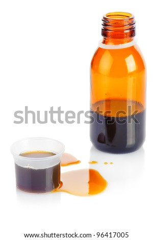 Pharmacy. Bottle and plastic measuring cup of syrup medication on white background - stock photo