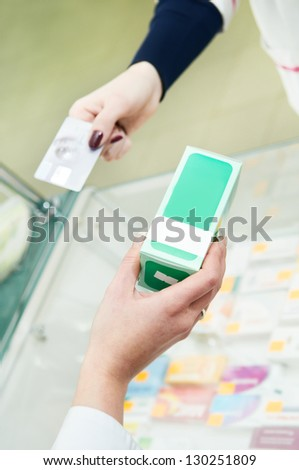 Pharmacy buying. Closeup hands of pharmacist with medicine and buyer with plastic card at drugstore - stock photo