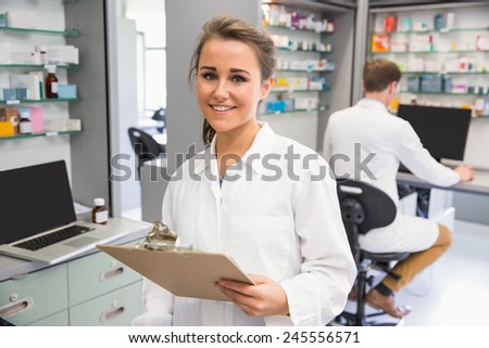 Pharmacy intern smiling at camera at the hospital pharmacy - stock photo