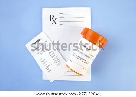 Pharmacy script with prescription bottle and receipt on blue. - stock photo