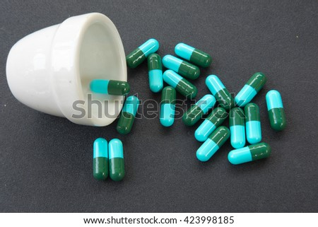 Pharmacy theme, Heap of blue green round capsule pills with medicine antibiotic - stock photo