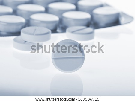 Pharmacy theme. Heap of white round medicine tablet pills and blister. Tinted in blue. - stock photo