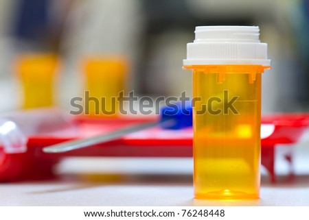 pharmacy vial ready to be filled, counting tray in the background - stock photo