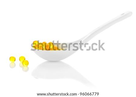 Pharmacy. Vitamin pills in spoon on white background - stock photo