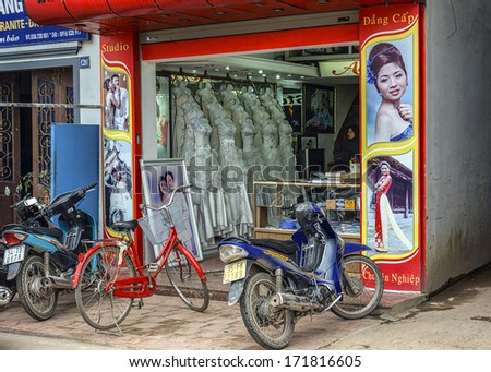 PHAT DIEM, VIETNAM - CIRCA MARCH 2012: Motorbikes in front of typical bridal store in small town displaying bridal gowns.