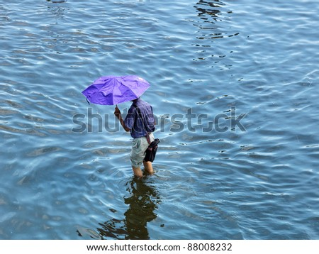 PHATHUMTRANI, THAILAND- OCTOBER 21: Man with umbrella walk on main road during the worst flooding disaster in decades on October 21, 2011 Rongsit Road, Phathumtrani, Thailand. - stock photo