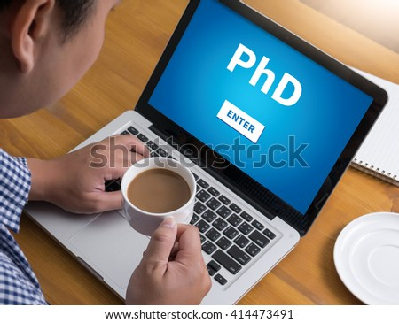 PhD Doctor of Philosophy Degree Education Graduation Businessman at work. Close-up top view of man working on laptop while sitting at the wooden desk , coffee - stock photo