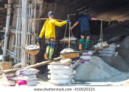 PHETCHABURI, THAILAND - APR 6 : Unidentified workers carrying salt at the salt farm on APRIL 6 , 2016 in Phetchaburi,Thailand. It is a salt production is one of a great wide industry of Phetchaburi