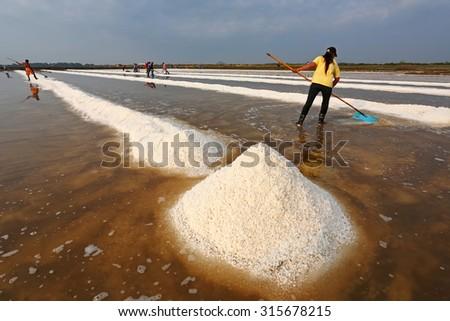 PHETCHABURI, THAILAND - FEB 11: Unidentified workers carrying salt at salt farm on February 11, 2012 in Phetchaburi,Thailand. It is a salt production is one of a great wide industry of  Phetchaburi  - stock photo