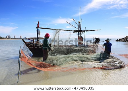 PHETCHABURI, THAILAND - JUN 29: Fishermen on the beach collecting fishing nets with fishing boat at Cha-am beach on June 29, 2015 in Phetchaburi, Thailand