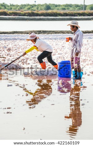 Phetchaburi,Thailand - May 15, 2016:Workers shoveled the salt crystallizes out of the ground in salt farm , filled with natural salt from the sea. This is one step in the production of sea salt.