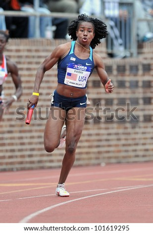 PHILADELPHIA - APRIL 28: Barbara Pierre from the USA runs the second leg of the sprint medley at the Penn Relays April 28, 2012 in Philadelphia. - stock photo