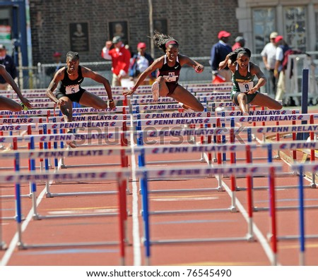 PHILADELPHIA - APRIL 30: Gabby Mayo from Texas A&M (center) clears a hurdle in the 100m College Ladies Hurdles Championship at the 117th Penn Relays on April 30, 2011 in Philadelphia, PA. - stock photo