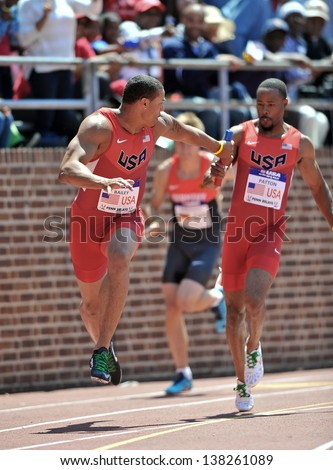 PHILADELPHIA - APRIL 27: Ryan Bailey, running for USA red, reaches for the baton for the anchor of the USA vs. the World 4x100 race at the 2013 Penn Relays April 27, 2013 in Philadelphia - stock photo