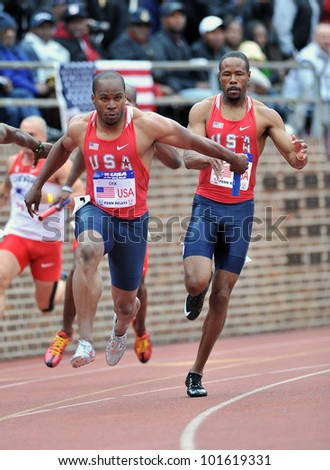 PHILADELPHIA - APRIL 28: Walter Dix from Team USA takes the baton for the anchor of a 4x100 USA vs the World heat at the Penn Relays April 28, 2012 in Philadelphia. - stock photo