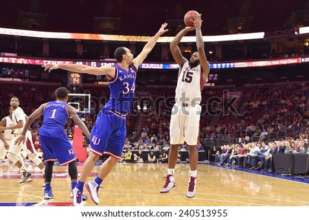 PHILADELPHIA - DECEMBER 22: Temple Owls forward Jaylen Bond (15) shoots over Kansas Jayhawks forward Perry Ellis (34) during the NCAA basketball game December 22, 2014 in Philadelphia.  - stock photo