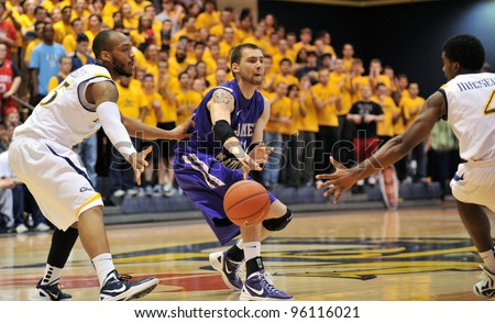 PHILADELPHIA - FEB 22: JMU forward Andrey Semenov (11) makes a bounce pass between two defenders during the NCAA basketball game between Drexel and James Madison February 22, 2012 in Philadelphia